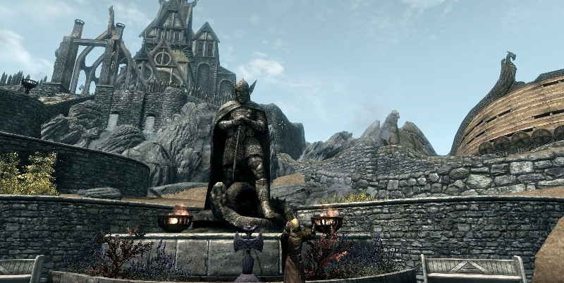 Statue of Talos in Whiterun, with Shrine in front, Dragonsreach to left, giant Eagle in middle, and old Companion's home to right.